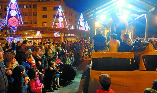 Entrada. Olentzero llegó en su gurdia a la plaza de San Juan, donde le esperaban cientos de niños, niñas, aitas y aitonas. /  FOTOS F. DE LA HERA