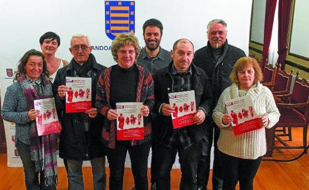 Participantes en la presentación de la Oficina de Atención a Víctimas del Franquismo muestran el folleto que se ha buzoneado./UNANUE