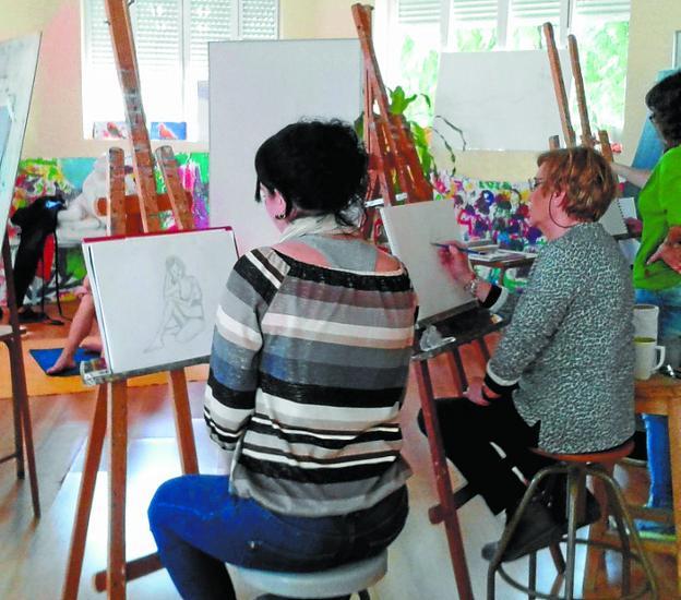 Alumnas pintan durante una de las clases de la academia. /
