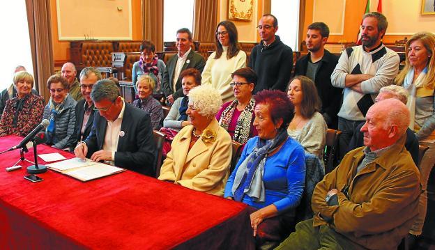 El alcalde firma el convenio bajo la mirada de representantes de la Comisión de Personas Mayores y de asociaciones de la ciudad, delegados del Gobierno municipal y portavoces y concejales de todos los grupos políticos del Ayuntamiento de Irun. /
