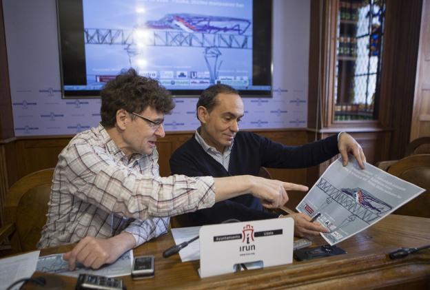 José Félix Colado y Miguel Ángel Páez comentan el cartel de la jornada de este año, que representa un tren del servicio Avlo cruzando el Puente Internacional de Irun ./F. DE LA HERA