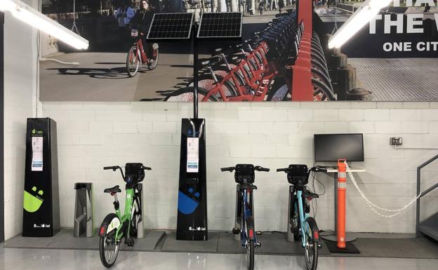 Varias bicicletas en sus anclajes y postes informativos con paneles solares.