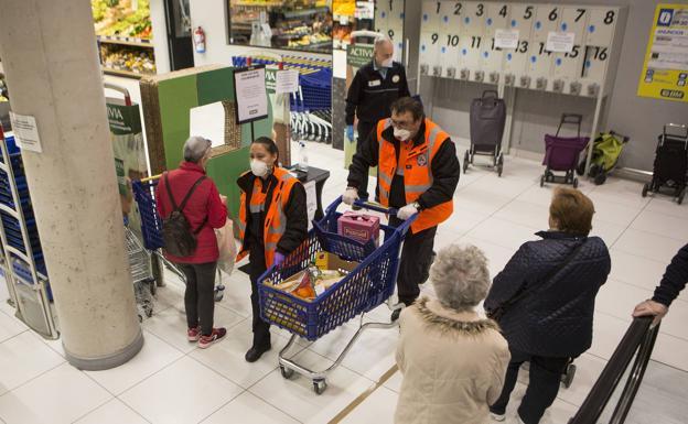 Dos voluntarios de Protección Civil de Irun compran alimentos en un establecimiento de la ciudad. /F. de la Hera