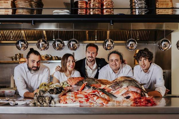 El equipo de Estimar Madrid posa con una amplia variedad de pescados y mariscos que harán las delicias de tus invitados.